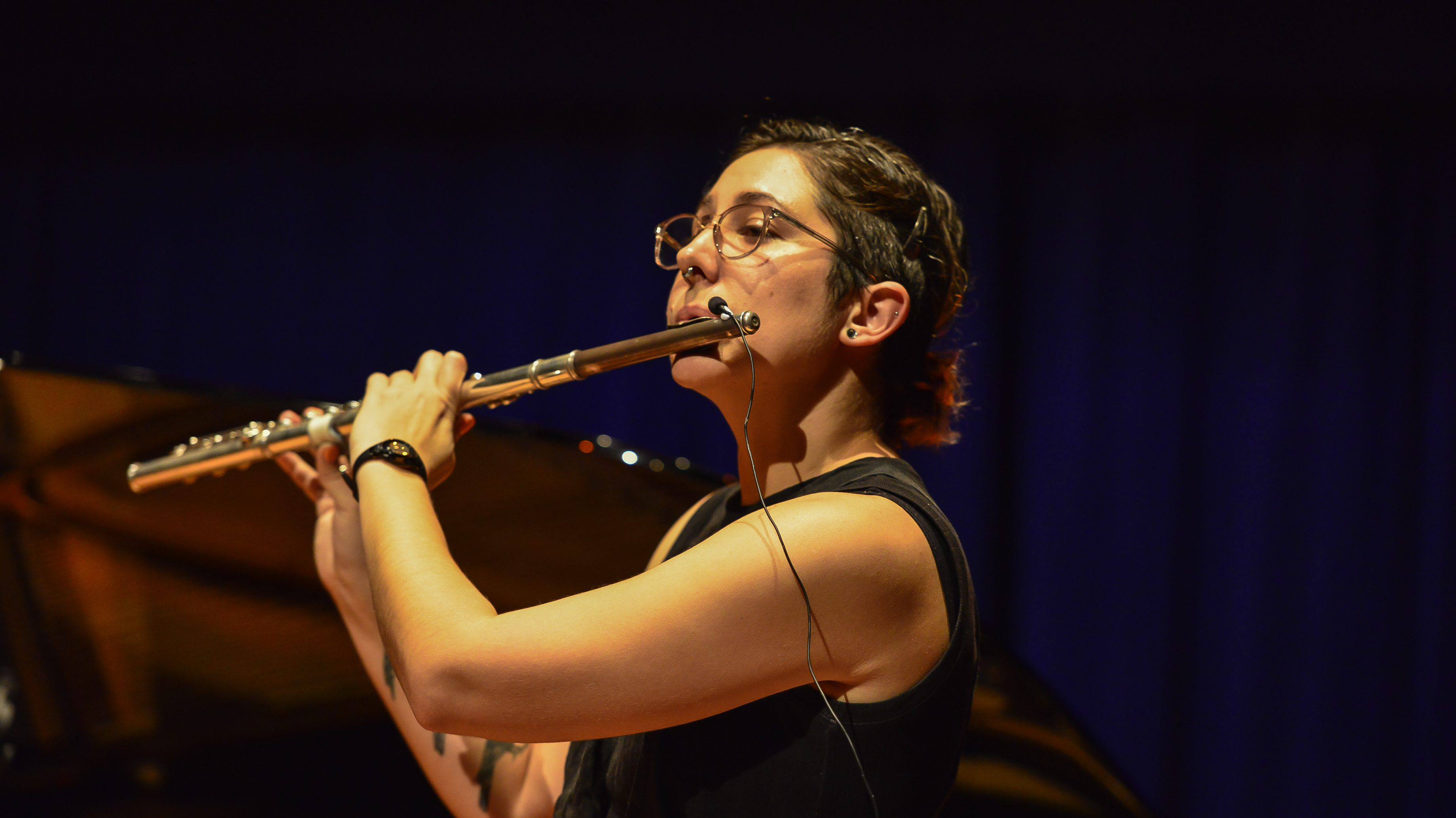 Olive-skinned girl with brown hair and glasses playing the flute. She wears a black sleeveless top and a black watch, and some tattoos on her right arm are visible, but partly obscured.